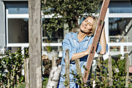 Woman relaxing in garden - JOSF00936