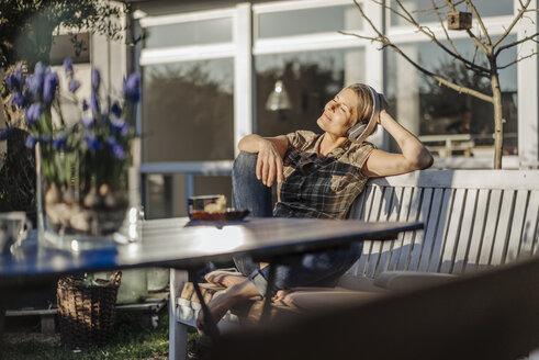 Woman wearing headphones relaxing on garden bench - JOSF00951