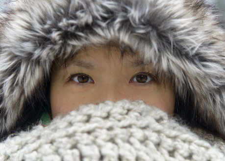 Portrait of woman wearing fur cap covering nose and mouth with scarf - TOVF00077