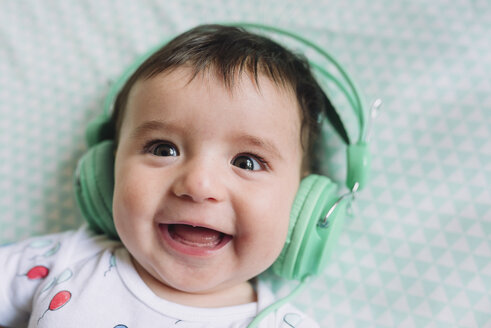 Portrait of laughing baby girl with headphones - GEMF01611