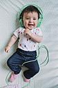 Portrait of happy baby girl with headphones lying on blanket - GEMF01614
