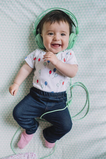 Portrait of happy baby girl with headphones lying on blanket - GEMF01614