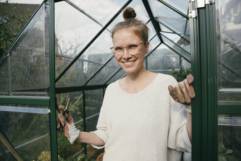 Portrait of smiling young woman standing in the door of her greenhouse - MFF03486
