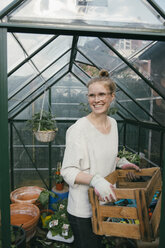 Portrait of smiling young woman with box of gardening tool in front of greenhouse - MFF03489