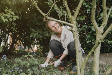 Smiling young woman clearing weeds in the garden - MFF03498