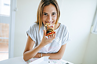 Portrait of young woman eating pizza at home - KIJF01478