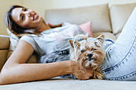 Portrait of Yorkshire Terrier lying on the couch with owner - KIJF01481