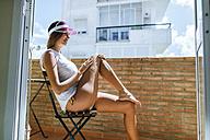 Woman sunbathing on a balcony - KIJF01484