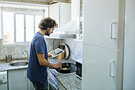 Man cooking in kitchen while looking at tablet - KIJF01487