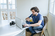 Man drinking vegetable juice while using laptop at home - KIJF01496