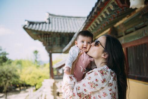 South Korea, Gyeongju, womankissing a baby girl in Bulguksa Temple - GEMF01619