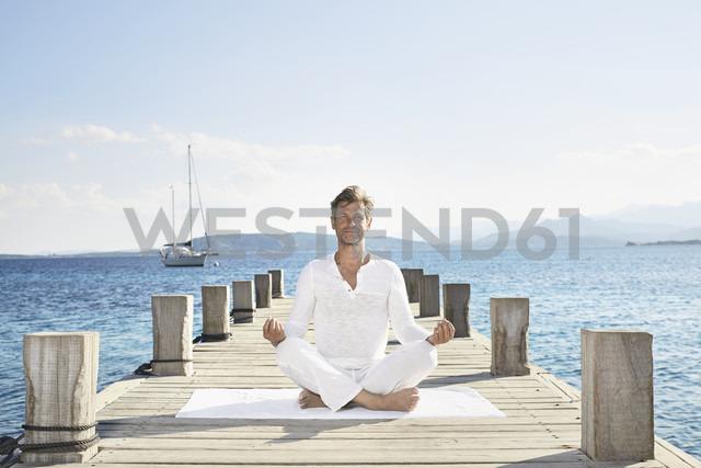 Mature man doing yoga exercise on jetty - PDF01230
