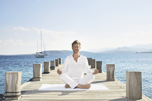Mature man doing yoga exercise on jetty - PDF01230