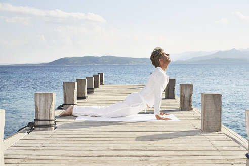 Mature man doing yoga exercise on jetty - PDF01233