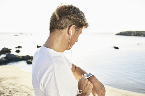 Mature man with earphone checking his smartwatch after yogging on the beach - PDF01242