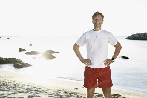 Portrait of confident mature man with earphones and smartwatch on the beach - PDF01245