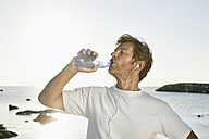 Mature man drinking water after jogging on the beach - PDF01248