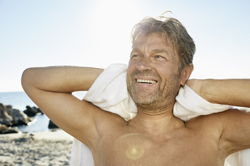 Portrait of smiling man with towel in front of the sea - PDF01257