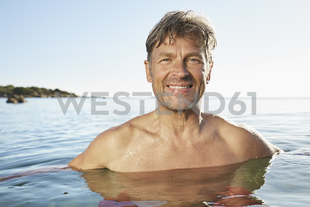 Portrait of smiling man bathing in the sea - PDF01260