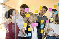 Business people discussing in front of glass screen with sticky notes - PESF00576