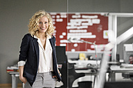 Dynamic businesswoman standing in office, smiling - PESF00579