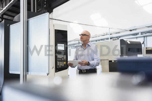 Man with tablet at machine on factory shop floor - DIGF02445