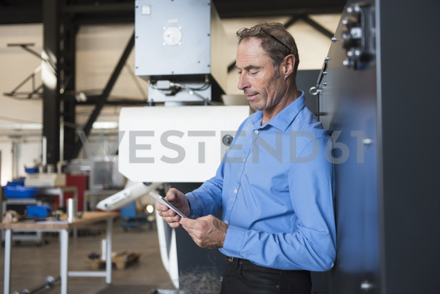 Man with cell phone on factory shop floor - DIGF02457