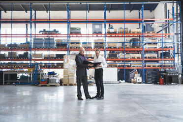 Two businessmen with clipboard on factory shop floor - DIGF02469