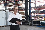 Man with documents on factory shop floor - DIGF02472