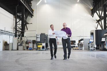 Two businessmen with plan walking in factory shop floor - DIGF02484