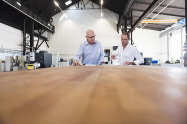 Two businessmen looking at plan on table in factory - DIGF02490