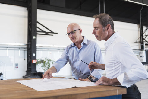 Two businessmen looking at plan on table in factory - DIGF02493