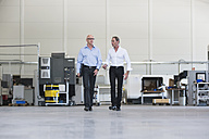 Two businessmen walking and talking in factory shop floor - DIGF02499