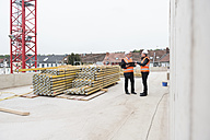 Two men wearing safety vests talking on construction site - DIGF02508