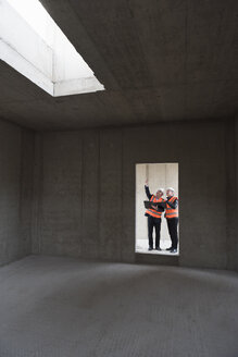 Two men wearing safety vests talking in building under construction - DIGF02511