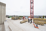 Two men with plan wearing safety vests talking on construction site - DIGF02514