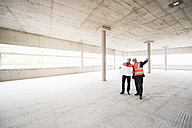 Two men with plan wearing safety vests talking in building under construction - DIGF02520