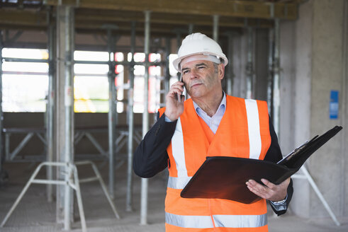 Man on the phone wearing safety vest in building under construction - DIGF02523