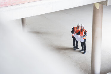 Two men with plan wearing safety vests talking in building under construction - DIGF02529