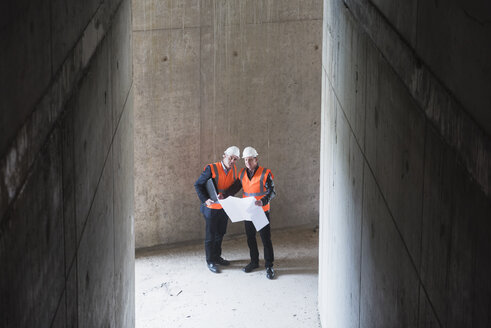Two men with plan wearing safety vests talking in building under construction - DIGF02532
