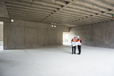 Two men with plan wearing safety vests talking in building under construction - DIGF02535