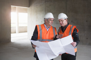 Two men with plan wearing safety vests talking in building under construction - DIGF02538