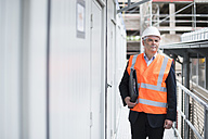 Man with documents wearing safety vest on construction site - DIGF02544