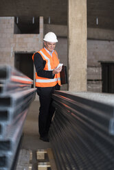 Man with cell phone wearing safety vest in building under construction - DIGF02547