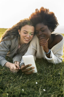 Two best friends lying in grass with cell phone - MGOF03341