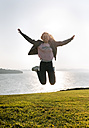 Teenage girl jumping at the coast - MGOF03350