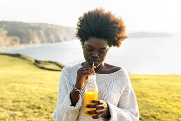 Young woman drinking orange juice at the coast - MGOF03359