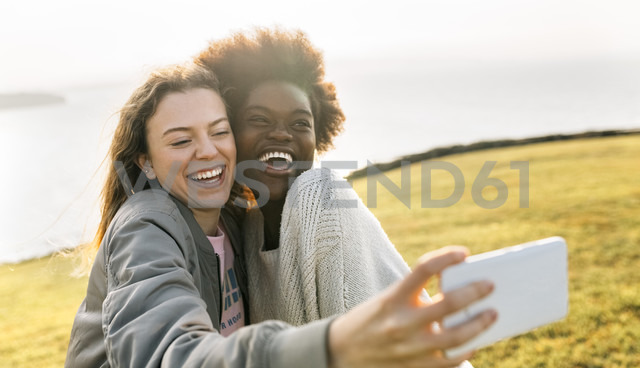 Two happy best friends making a selfie at the coast - MGOF03362