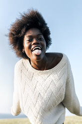 Portrait of young woman sticking her tongue out - MGOF03371