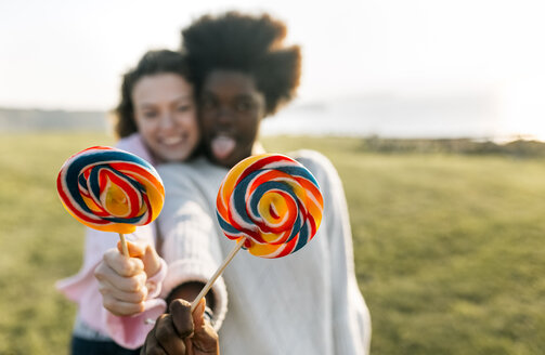 Two best friends having fun with lollipops outdoors - MGOF03374